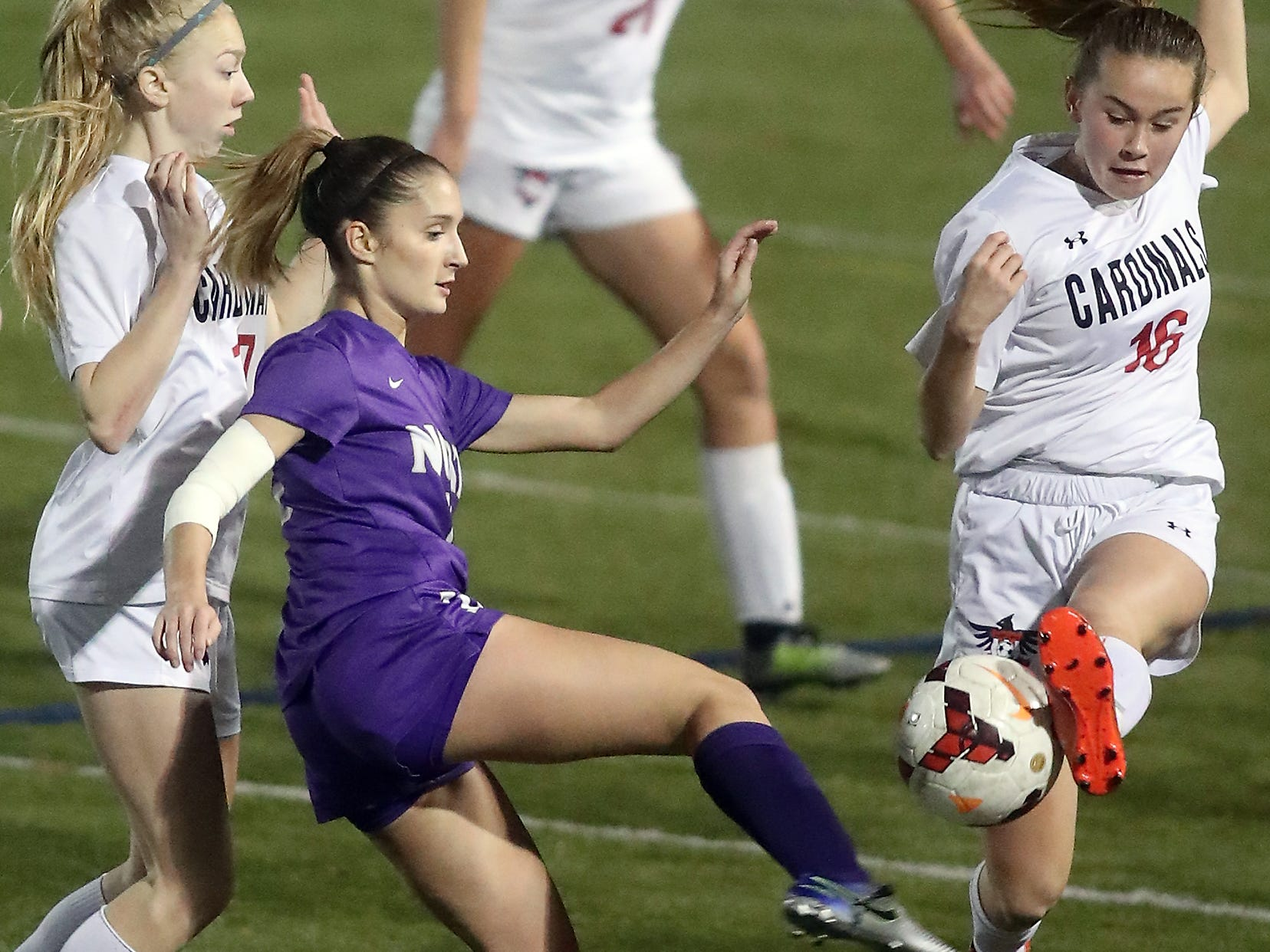 North Kitsap's Emily DeLay (center) battles for control of the ball with vs Orting's Bella Southwell (left) and Jenna Witham (right) in Poulsbo on Tuesday, October 30, 2018.