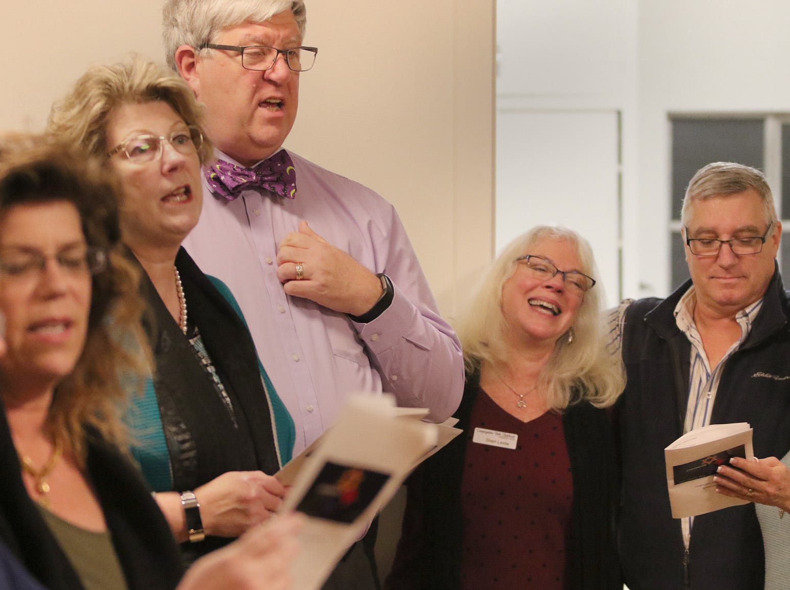 """The Beth Hatikvah (House of Hope) Synagogue in Bremerton held a memorial service for the Tree of Life Synagogue shootings Tuesday night in Bremerton. Joining in singing """"This Little Light of Mine"""" at right are, Sharil Leslie, left, and David and Bari Udell."""