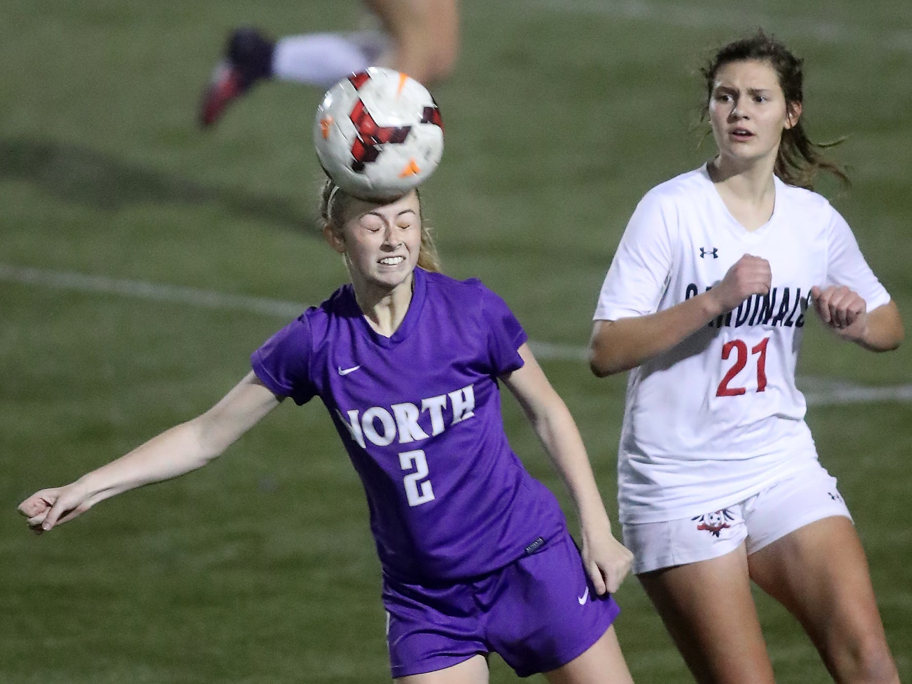 Orting's Hailey Hansen (21) looks on as North Kitsap's Mia St. Peter (2) connects with a header during their game in Poulsbo on Tuesday, October 30, 2018.