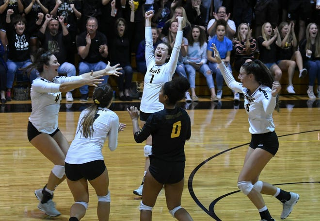 Merritt Island volleyball players celebrate their win over Bishop Moore during Tuesday regional semifinal.