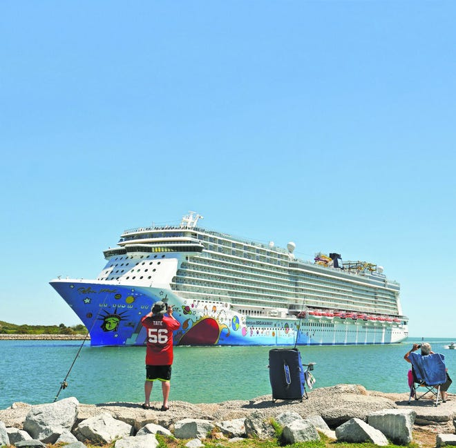 People fishing at Port Canaveral watch the Norwegian Breakaway sail past them.f the port's current budget year.