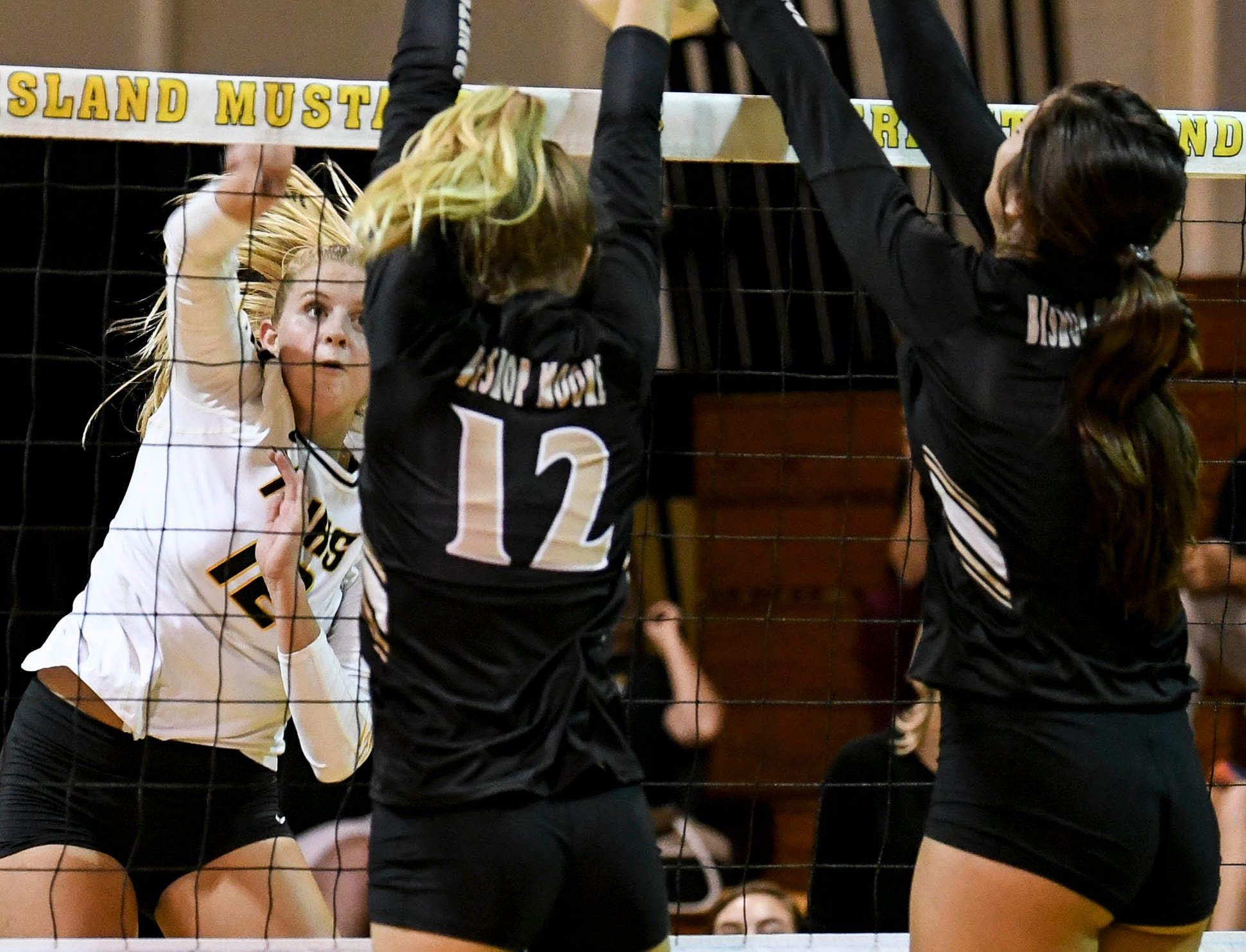 Bishop Moore players block a spike by Bobbie Jo Schwantz during Tuesday volleyball regional semifinal.