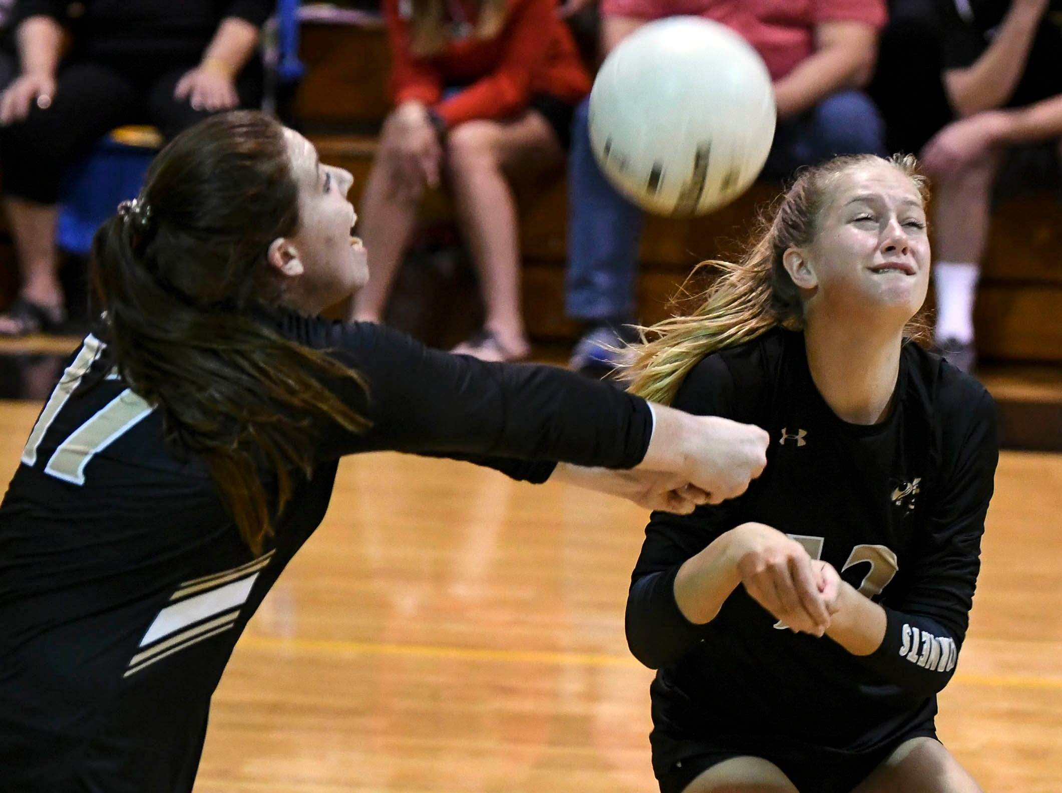 Two Bishop Moore players go for the same ball during Tuesday volleyball regional semifinal.