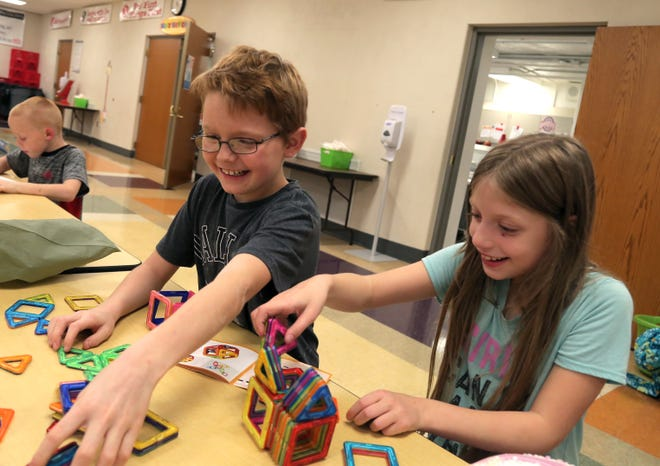 Dominic Williams, 11, and Carey Campbell, 8, work on putting together a magnet game during the after-school activities at Bucyrus Elementary school on Tuesday. The school offers dinner, homework assistance, enrichment classes and other activities through a federal grant via the state of Ohio's Department of Education.