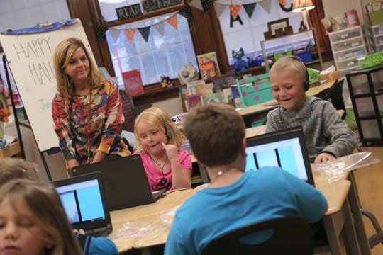 First-grade teacher Amy Hawkins watches as Summer Hall and Brandon Thomson, both 7, complete educational games during the after school program at Bucyrus Elementary school on Tuesday.
