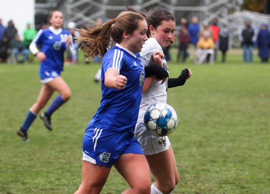 Colchester's Emma Corriveau, left, and Annalise Lubas of Essex chase down a 50-50 ballduring Wednesday's Division I girls soccer semifinal in Colchester.