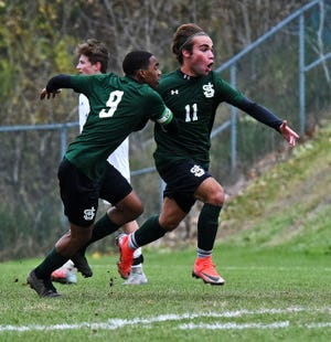 Pablo Gonzalez-Rotger (11) and Malik Joell react after Gonzalez-Rotger's first-half goal during No. 2 St. J Academy's 2-1 win over No. 3 Essex in a Division I boys soccer semifinal in St. Johnsbury on Tuesday, Oct. 30, 2018.