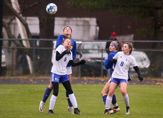 Milton's Morgan Bushey, left, and Elizabeth Poirier fight for a header against Erika Williams (6) and Sasha Kennedy of U-32 during Wednesday's Division II girls soccer semifinal in Milton.