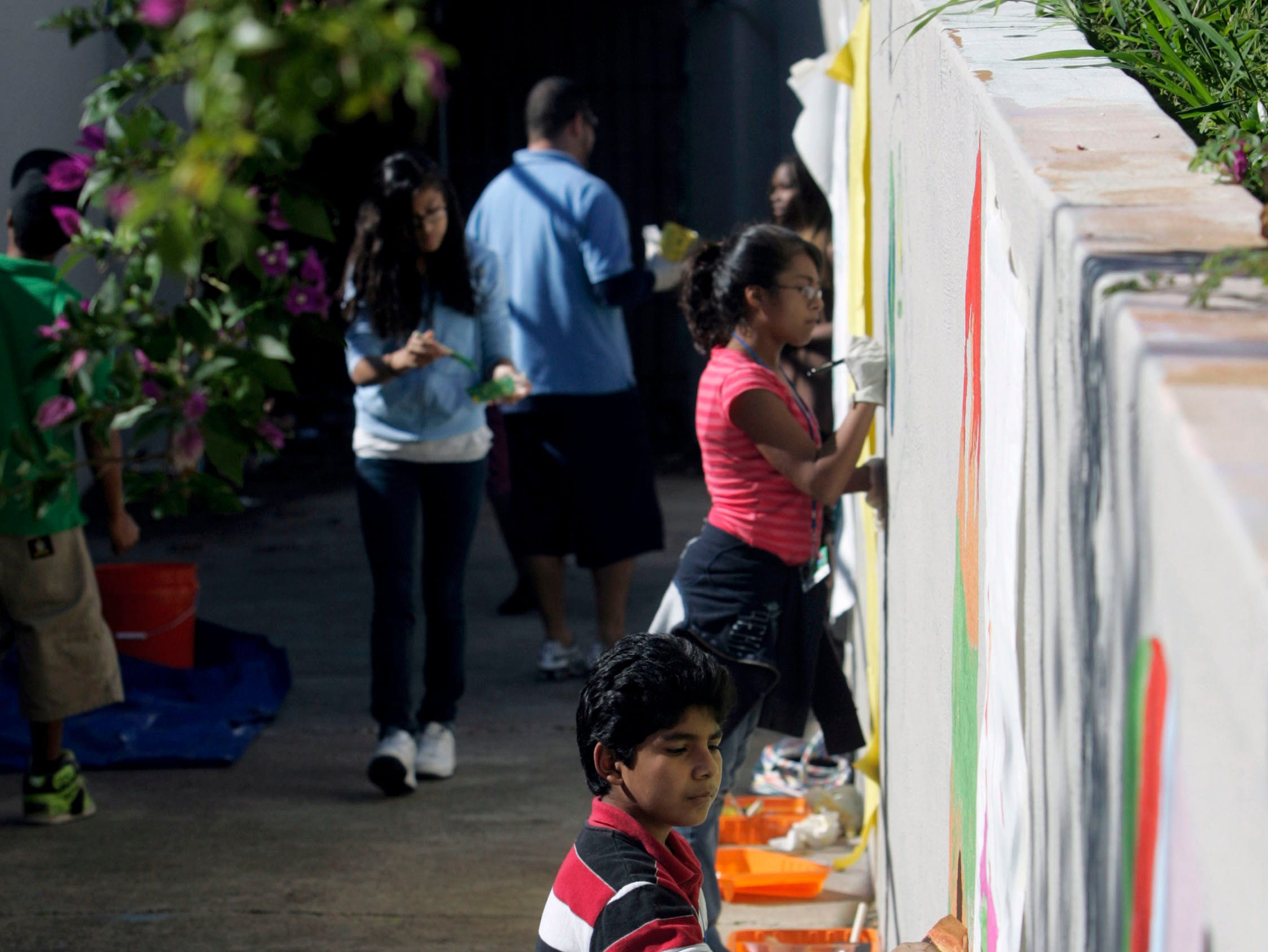 Jacob Harris, 10 (bottom center), works with other children to paint surfboard murals Wednesday, Nov. 25, 2009 along the walls leading to the entrance of the old bluff tunnel at La Retama Park in Corpus Christi.