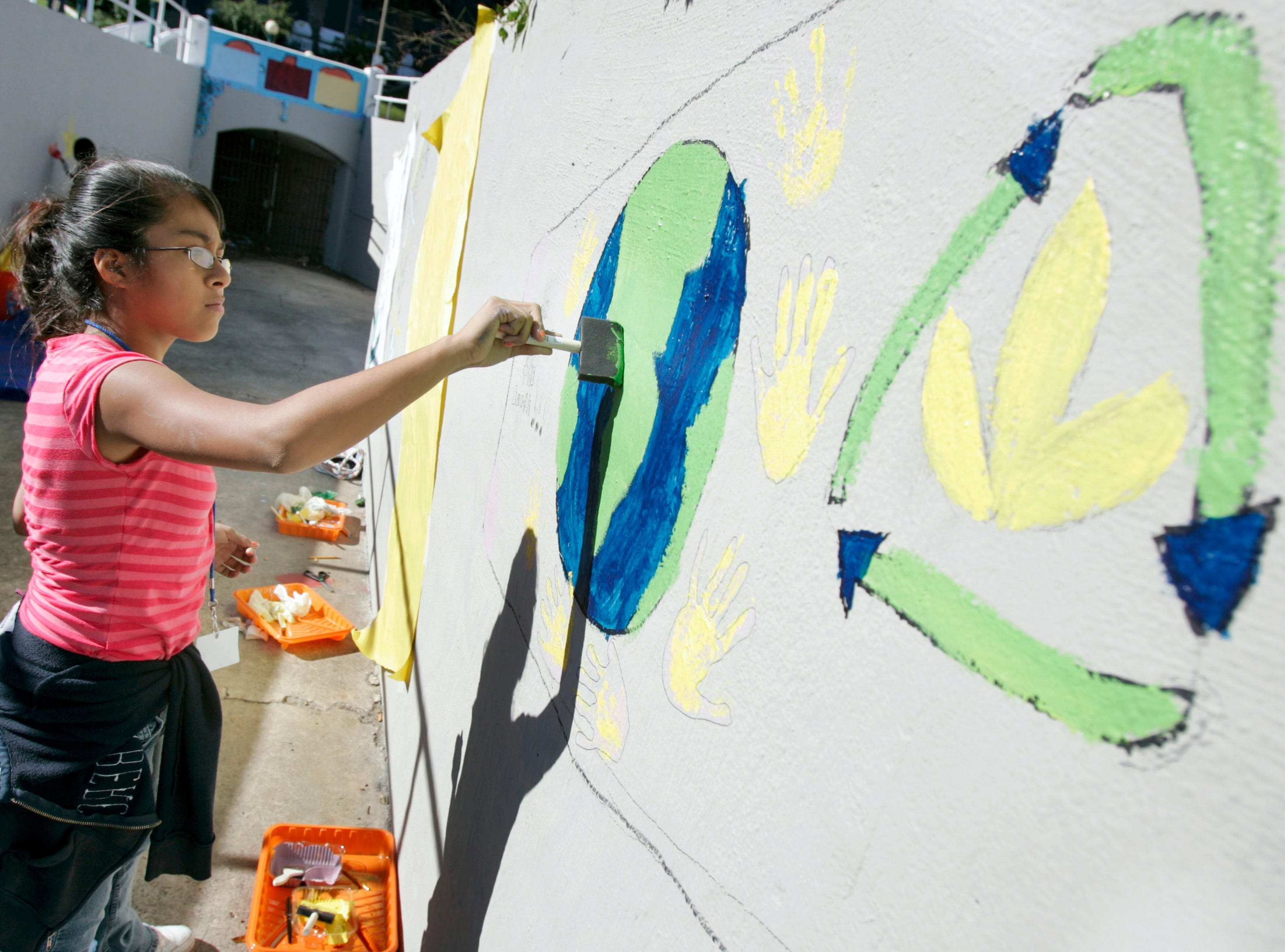 Leesa Hernandez, 12, a member of the Oso Recreation Center, works on an earth-friendly surfboard mural Wednesday, Nov. 25, 2009 on the walls leading to the entrance of the old bluff tunnel by La Retama Park in downtown Corpus Christi. Several children aged 13-17 participated in the Operation Surfboard art project.