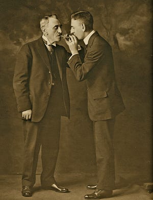 'Rube and Father Lighting Cigars,' date unknown, is a photograph by Rube Goldberg. Copyright © Rube Goldberg Inc. All Rights Reserved. RUBE GOLDBERG ® is a registered trademark of Rube Goldberg Inc. All materials used with permission. www.rubegoldberg.com