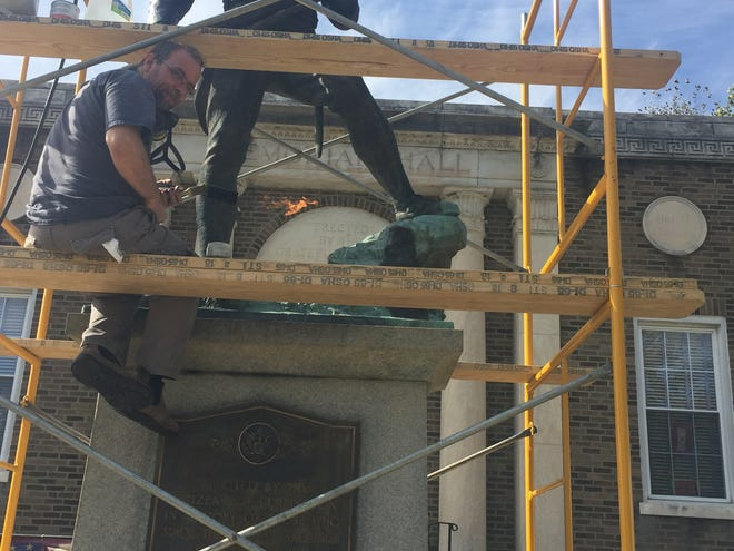 """Adam Jenkins wields a blow torch to help restore the """"Rock of the Marne, """" a Doughboy statue of a World War I soldier in Burlington City.  A re-dedication is set for Veterans Day following a morning parade ."""