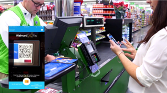 A Walmart photo illustration shows the Walmart app being used in a checkout lane.