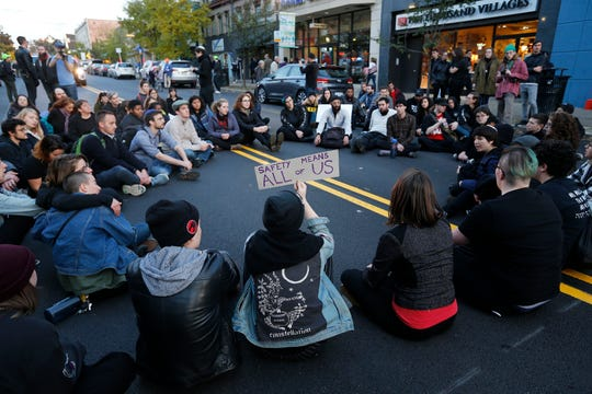 "A group of protesters sit in the middle of Forbes Avenue in the Squirrel Hill neighborhood  after the ""Safety Through Solidarity - No Antisemitism No White Nationalism"" and ""Stand together in solidarity with the Pittsburgh Jewish Community."""