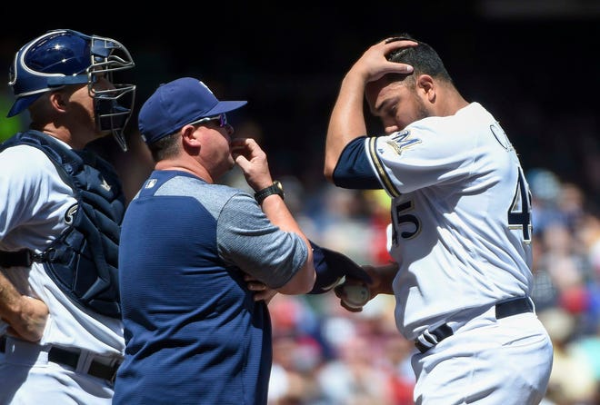 Jun 24, 2018; Milwaukee, WI, USA; Milwaukee Brewers pitcher Jhoulys Chacin (45) talks to pitching coach Derek Johnson and catcher Erik Kratz (15) in the fourth inning during the game against the St. Louis Cardinals at Miller Park. Mandatory Credit: Benny Sieu-USA TODAY Sports