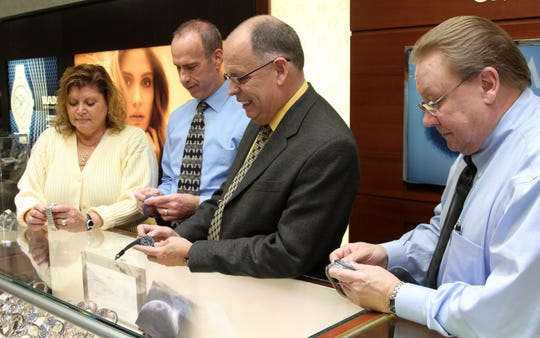 It's time to fall back. Here, Fords Jewelers store manager Albert Dahl (second from right), along with sales associates Debra Saparito (left) Mitch Yellin (second from left) and Alan Nygard are shown turning back some of the watches in the store. This weekend ends daylight saving time, and on Sunday, we switch back the clocks and get an extra hour of sleep.