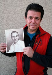 This Tuesday, Oct. 30, 2018, photo provided by Reuben Ortiz, shows Ortiz holding a photo of the Rev. Jerome Coyle in Albuquerque, N.M. Ortiz says he was angered to learn that Coyle, who had been living at his home until recently, admitted in 1986 that he sexually abused 50 Iowa boys and that the church has kept it quiet for decades.