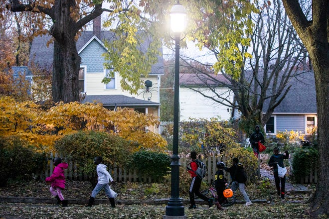 Children make their through the Sherman Hill neighborhood, ready to fill their candy buckets, on Beggars' Night, Tuesday, Oct. 30, 2018, in Des Moines.