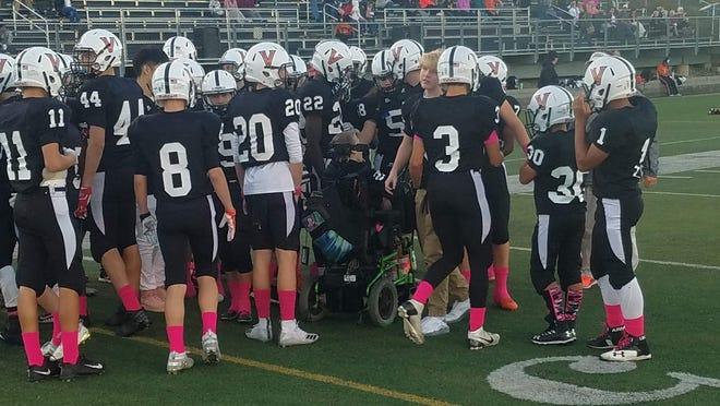 The Valley Southwoods football team huddles around Sam Wedig at Valley Stadium.