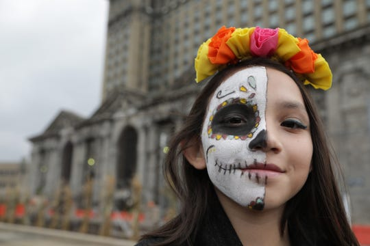 Alyiah Sierra, 10, of Detroit had her mother Maria Poland paint a sugar skull on half her face for trick-or-treating at the Michigan Central Station for a special Halloween party Wednesday, Oct. 31, 2018.