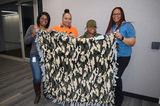 Jevetta Mooney, Zakiya Watt, Victoria Berry, and Cylie Watkins showing off their finished product during a blanket tying Community Service event at Credit Acceptance Corporation.