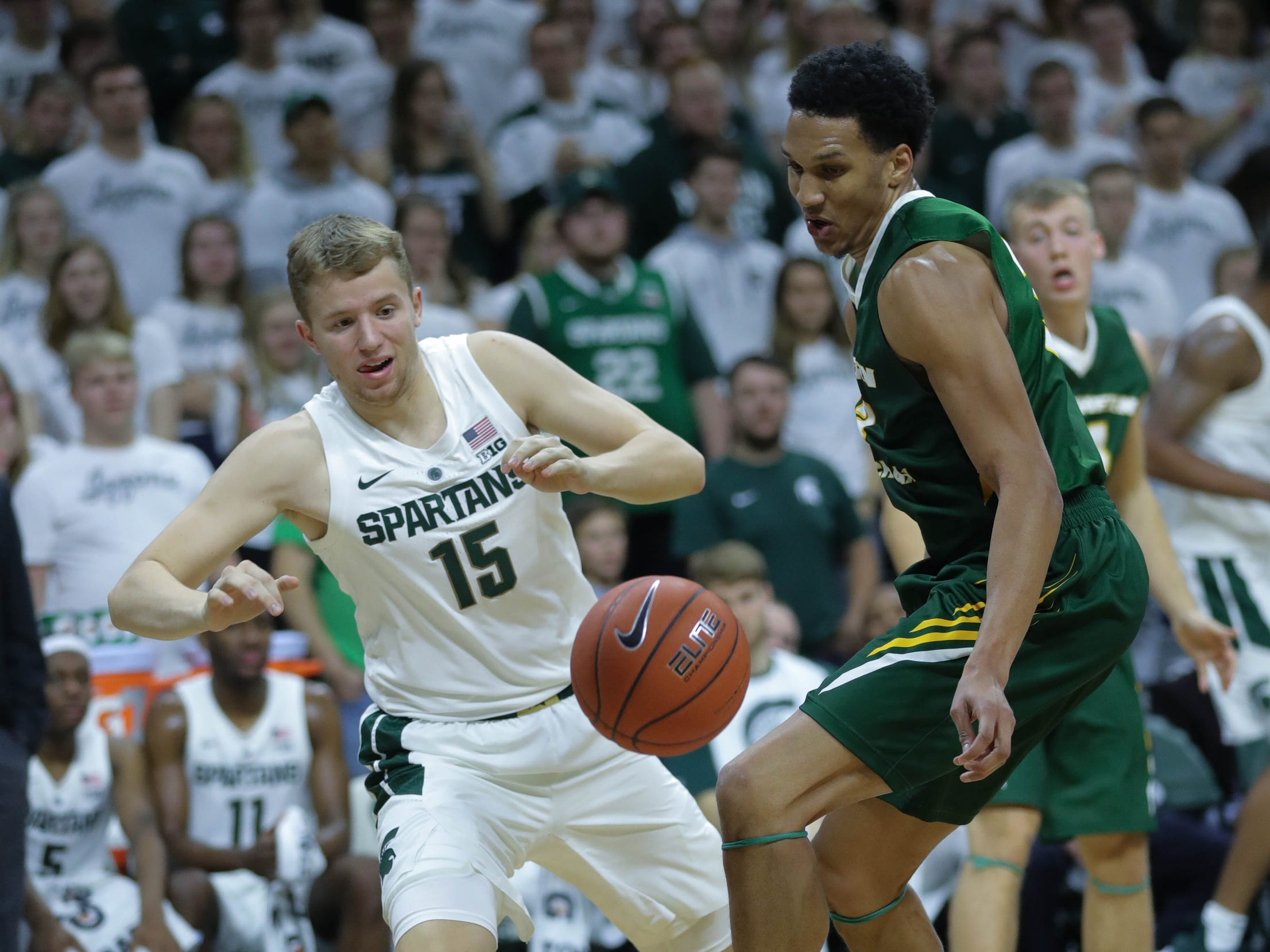 Michigan State forward Thomas Kithier goes for the loose ball against Northern Michigan Myles Howard during second half action Tuesday, October 30, 2018 at the Breslin Center in East Lansing, Mich.