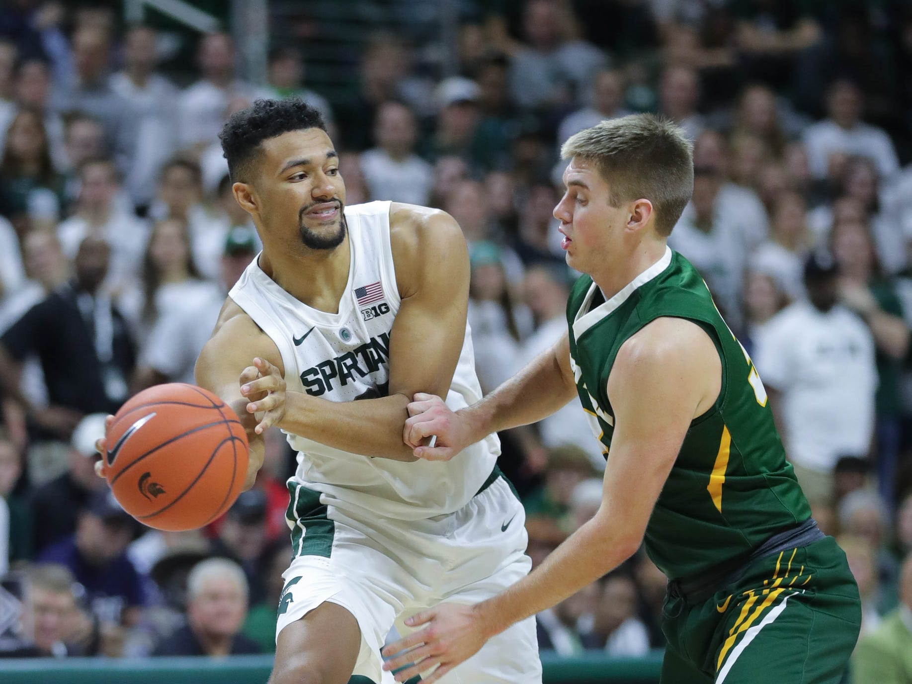 Michigan State forward Kenny Goins passes against Northern Michigan forward Marcus Matelski during second half action Tuesday, October 30, 2018 at the Breslin Center in East Lansing, Mich.