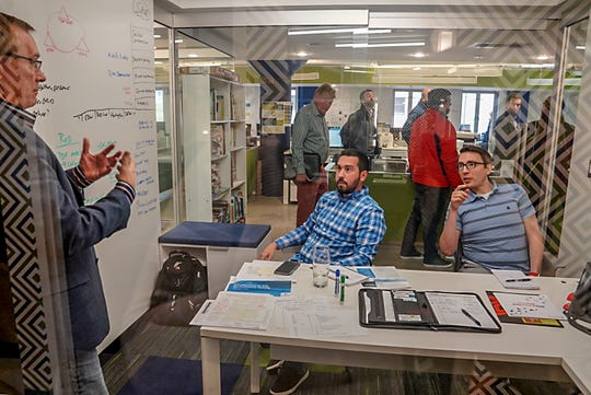 Chief Technology Officer Jeff Babler leads a discussion with controller Tom Lauer and IT business analyst Brandon Mccandlish in one the conference rooms at Sachse Construction in downtown Detroit  on Friday, Oct. 26, 2018.