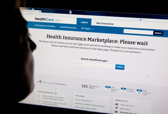 "A woman looks at the HealthCare.gov insurance exchange internet site showing a ""Please wait"" page, in this October 1, 2013 file photo in Washington, DC."