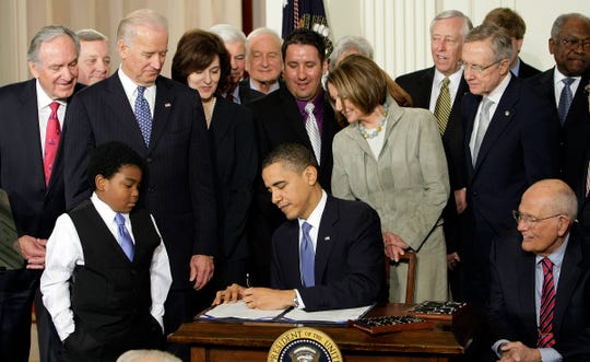 In this March 23, 2010, file photo, Marcelas Owens of Seattle, left, Rep. John Dingell, D-Mich., right, and others, watch as President Barack Obama signs the health care bill in the East Room of the White House in Washington.