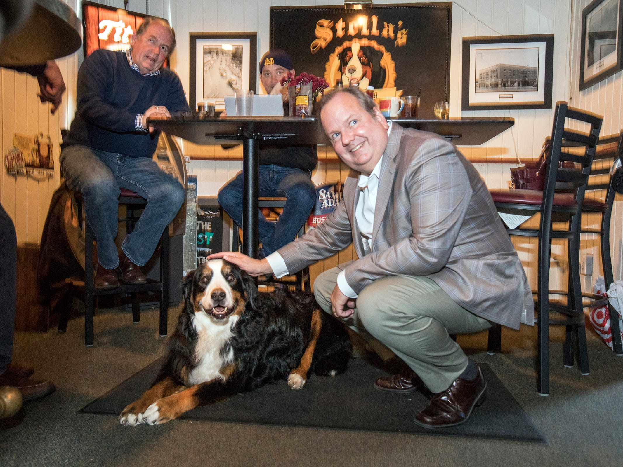 From left, Stella's Black Dog Tavern owners Bob Ostendorf, and Jim Sullivan are joined by Plymouth Township Supervisor Kurt Heise for the birthday party for Ostendorf's dog Stella at the tavern in Plymouth on Monday, Oct. 22, 2018.