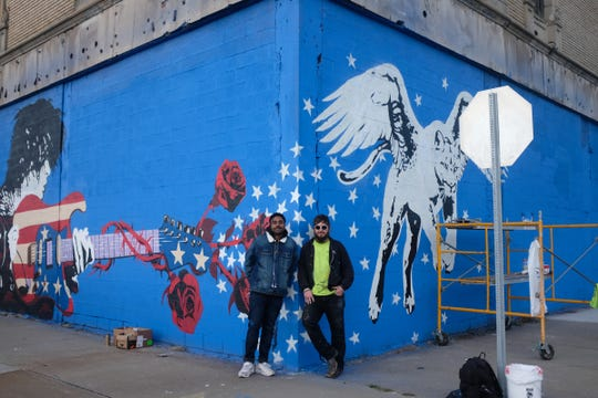 An in-progress version of the new MC5-inspired mural at the Grande Ballroom. Los Angeles artist Gabe Gault (left) worked alongside Detroit artist and sign painter Zak Warmann on the piece.