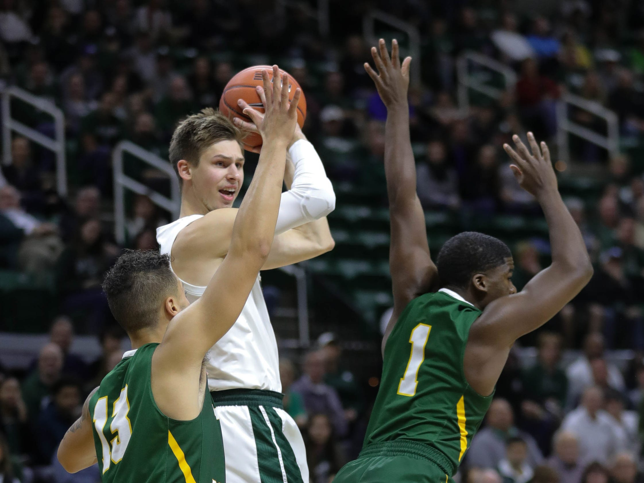 Michigan State guard Matt McQuaid passes against Northern Michigan defenders during the first half Tuesday, Oct. 30, 2018 at the Breslin Center in East Lansing.