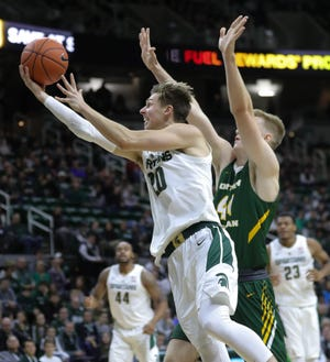 Michigan State guard Matt NcQuaid scores against Northern Michigan forward Troy Summers during first half action Tuesday, October 30, 2018 at the Breslin Center in East Lansing, Mich.