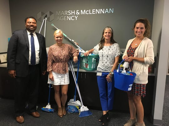 Marsh & McLennan Companies employees pose for a photo with donations gathered for Community Housing Network.