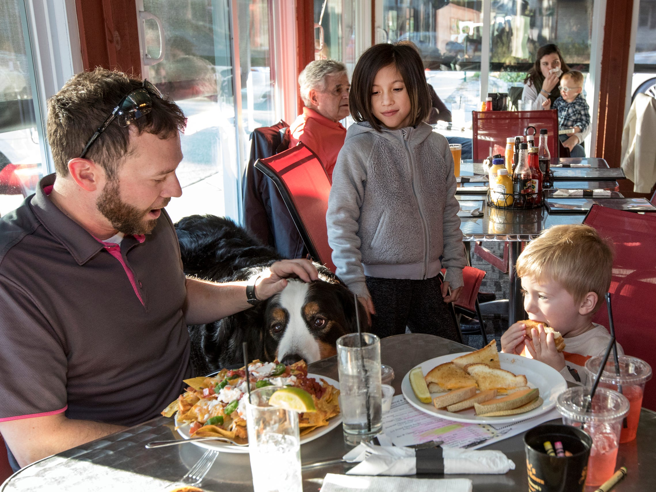 From left, Plymouth City Commissioner Marques Thomey, Leila Gatmaitan, 8 and Dean Thomey, 3, all of Plymouth, receive a visit from Stella at their table during her 8th birthday celebration at Stella's Black Dog Tavern in Plymouth on Monday, Oct. 22, 2018.