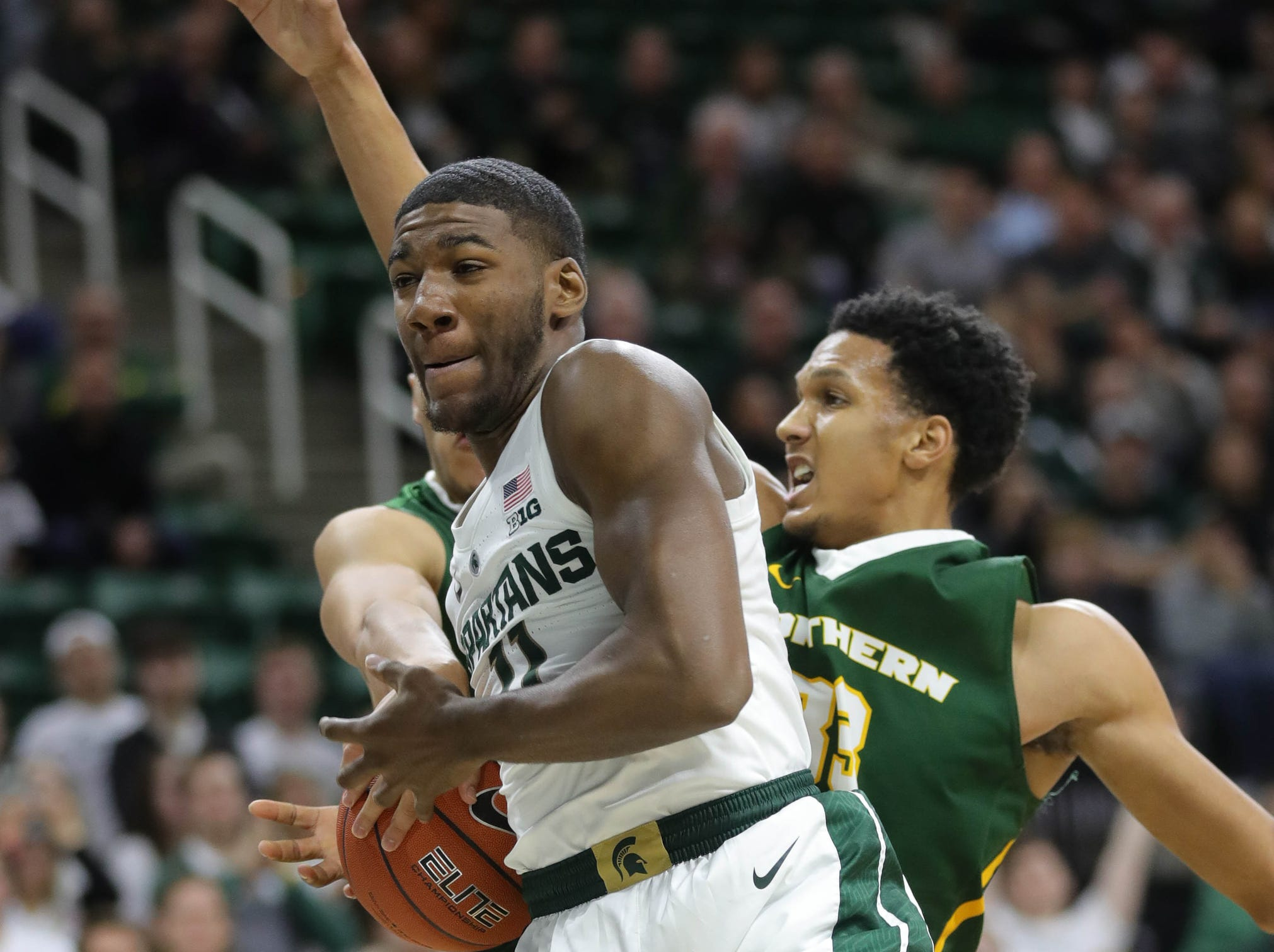 Michigan State forward Aaron Henry rebounds against Northern Michigan center Miles Howard during first half action Tuesday, October 30, 2018 at the Breslin Center in East Lansing, Mich.
