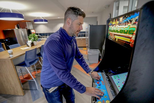 Sean Fossee, CEO, plays on the arcade machine in the breakroom at Custom Home Health & Custom Hospice in the new offices in Troy, Mich., on Tuesday, Oct. 2, 2018.
