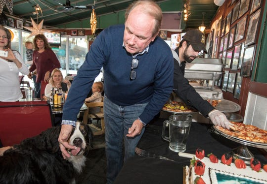 Stella licks icing from the finger of tavern owner Bob Ostendorf during a party for her 8th birthday at Stella's Black Dog Tavern in Plymouth on Monday, Oct. 22, 2018.