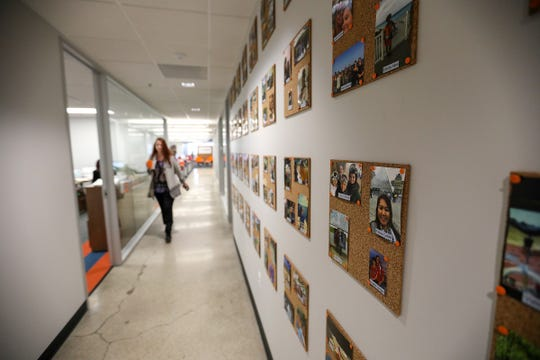 Personal photos of workers line the hallway at Custom Home Health & Custom Hospice,  in their new offices in Troy, Mich., on Tuesday, Oct. 2, 2018.
