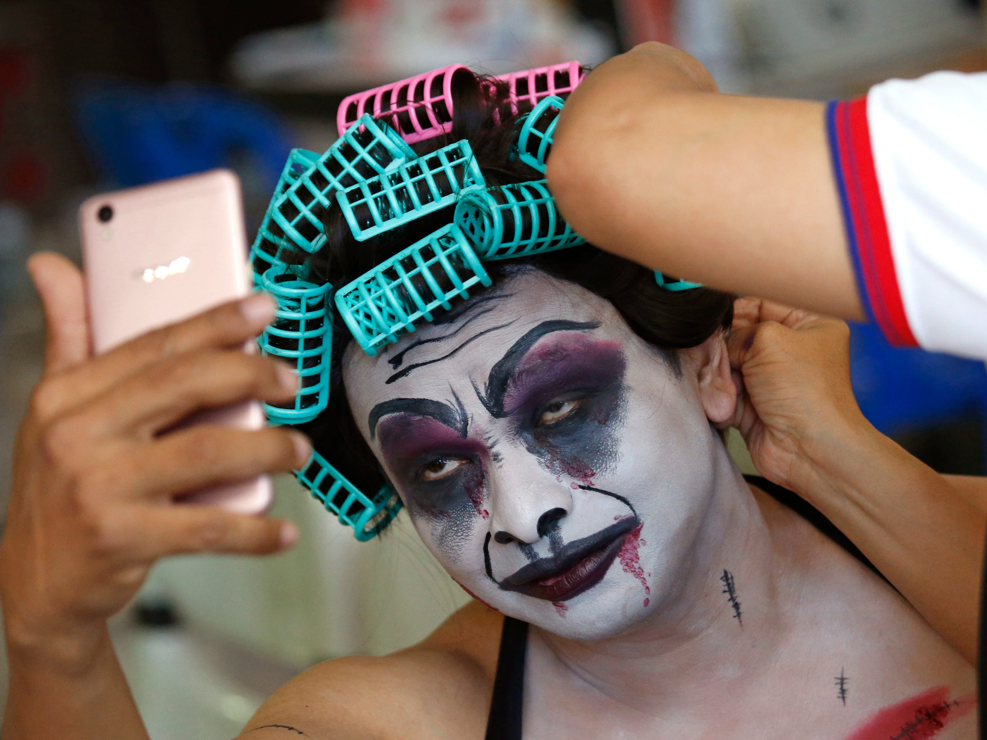 Thanat Chotrat gets made up in a ghost costume for Halloween before donating blood at the Thai Red Cross in Bangkok, Thailand, Wednesday, Oct. 31, 2018.