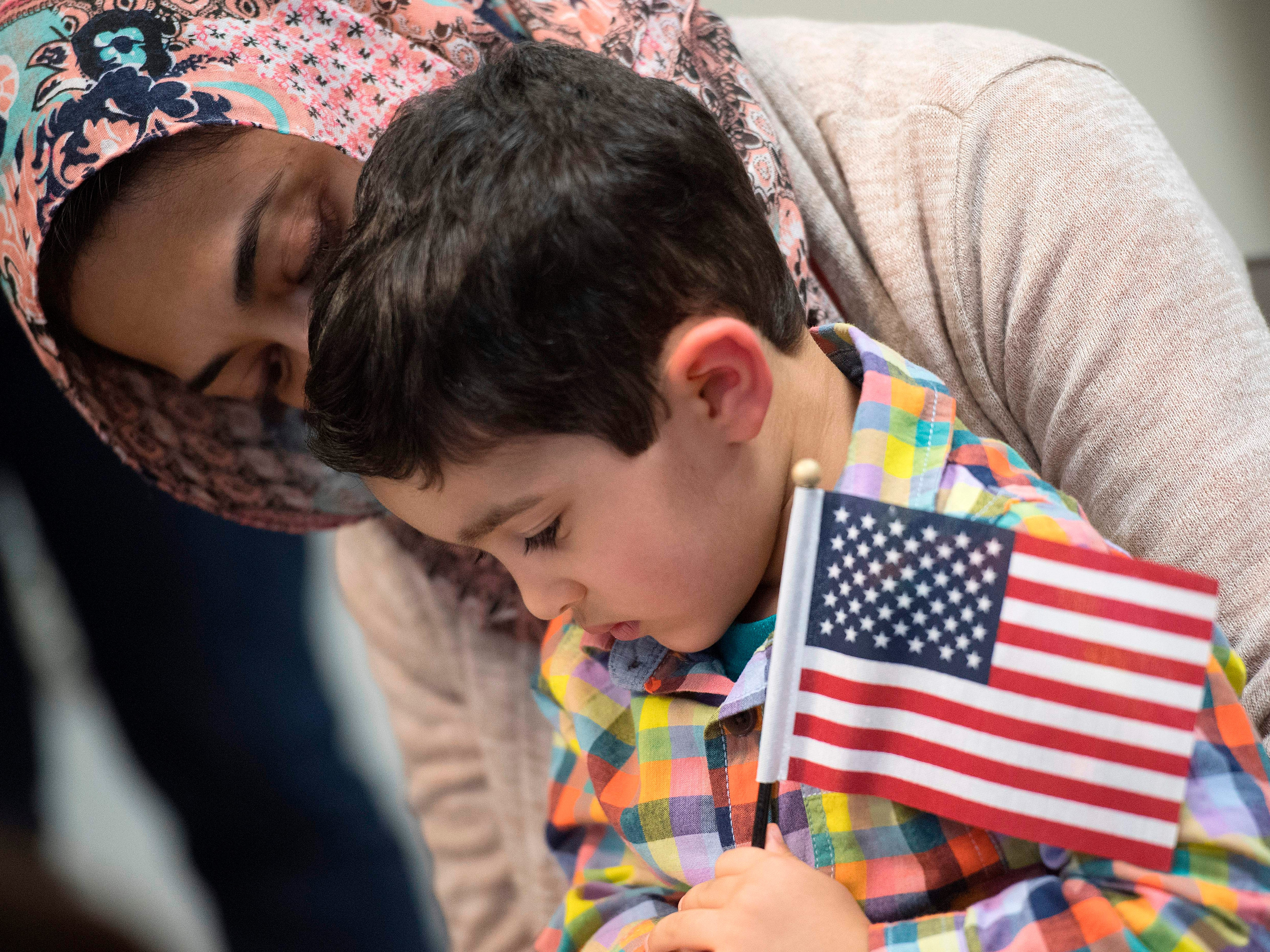 A boy is held by his mother as 35 children from 22 countries celebrate their U.S. citizenship during a special Halloween-themed ceremony at the U.S. Citizenship and Immigration Services Washington District Office in Fairfax, Virginia, on Oct. 31, 2018.