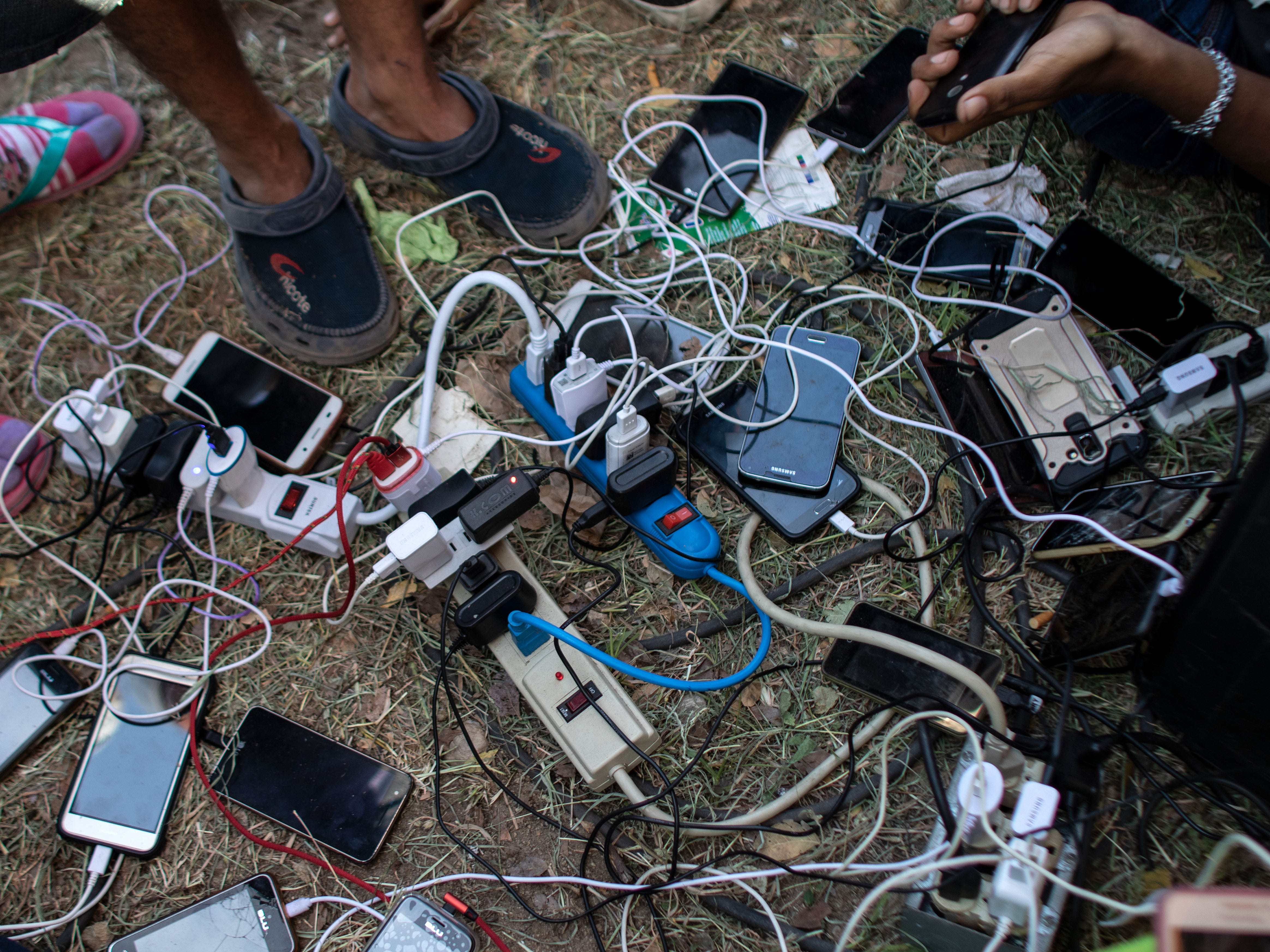 Honduran migrants taking part in a caravan heading to the U.S. charge their mobile phones at a temporary shelter in Juchitan de Zaragoza, Oaxaca state, Mexico on Oct. 30, 2018.