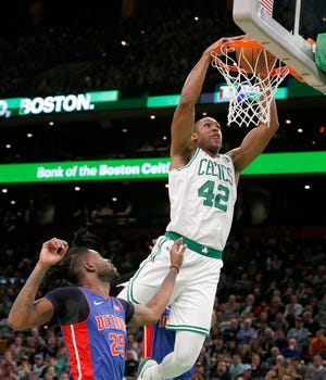 Boston Celtics center Al Horford (42) dunks the ball ahead of Detroit Pistons guard Reggie Bullock (25) during the first half.