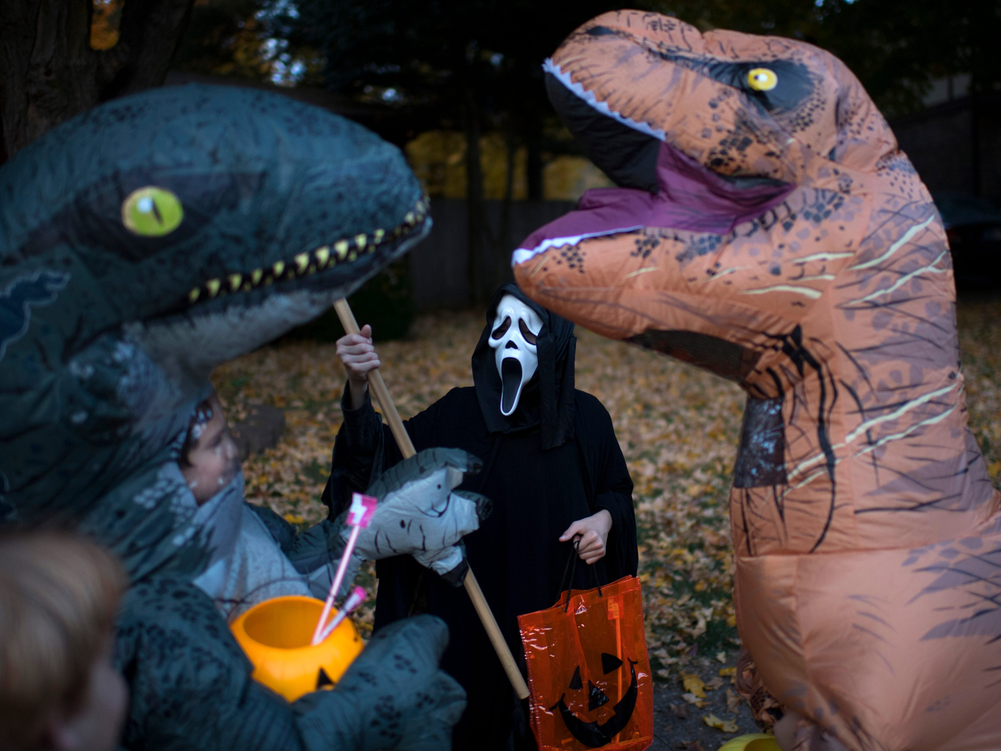 The streets of Newburgh, Ind., were chocked full of dinosaurs, monsters and Disney princesses as Halloween trick or treating was held a day earlier than usual Tuesday evening. Rain is forecast at a 100-percent chance for Halloween.