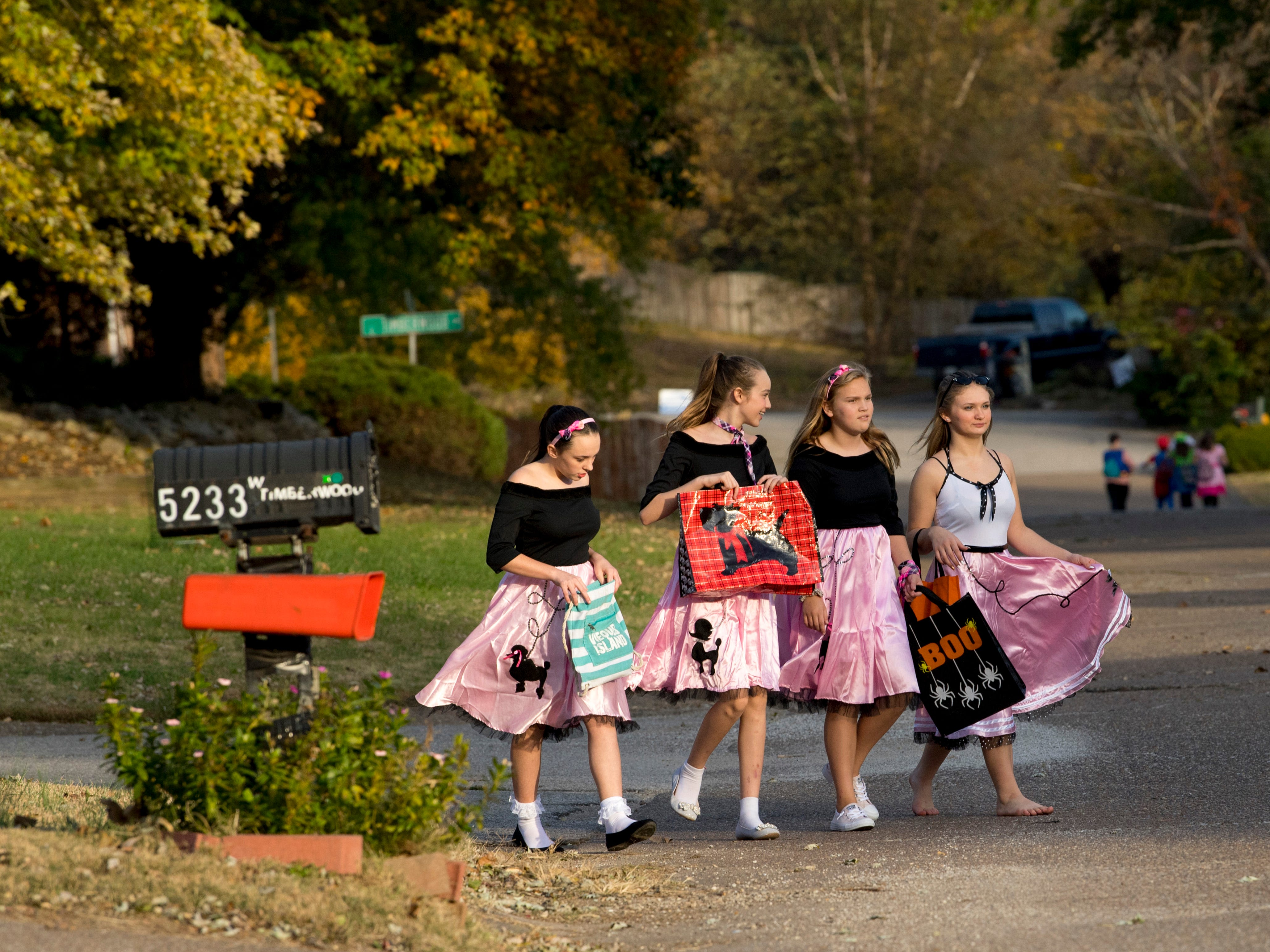 A group of bobby soxers head out in search of candy in Newburgh, Ind., Tuesday evening.