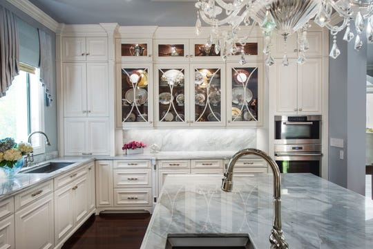 A backsplash wall behind the Wolf stove is filled with sparkling gems that complement the chandelier.