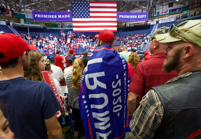 Sawyer Larson, of Fort Myers, drapes himself with a Trump flag while attending the Make America Great Rally at Hertz Arena I n Wednesday.