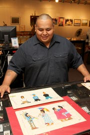 John Isaiah Pepion shows some of his newer contemporary art in comparison to more of his traditional work that can be viewed and bought at the Blackfeet Heritage Center in Browning in this Tribune file photo. His latest project is a wool blanket with ledger art influences.