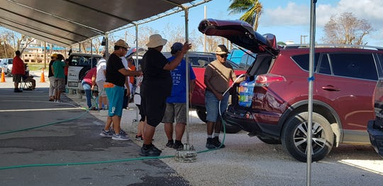 People wait for their turn to fill up their 5-gallon containers with drinking water at the Garapan Fishing Base on Saipan Wednesday. The military set up a reverse osmosis system that converts sea water into fresh drinking water, days after Super Typhoon Yutu caused massive water and power outages on Saipan and Tinian.